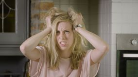 Beautiful blond woman going crazy messing up her hair looking at the camera stock video