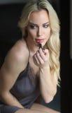 Beautiful Blond Woman with Green Eyes Applying Lipstick Stock Photo