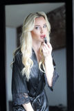 Beautiful Blond Woman with Green Eyes Applying Lipstick Royalty Free Stock Images