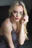 Beautiful Blond Woman with Green Eyes Applying Mascara Stock Photo