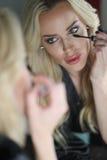 Beautiful Blond Woman with Green Eyes Applying Mascara Royalty Free Stock Photos