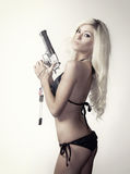 Beautiful blond woman with gun. Beautiful sexy blond young woman holding pistol gun and dog tag chains wearing bikini Royalty Free Stock Image