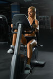 Beautiful blond woman in gym on bike Royalty Free Stock Photos