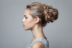 Beautiful Blond Woman. Hairstyle and Make-up. On gray background Royalty Free Stock Photos