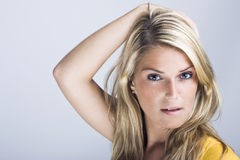 Beautiful blond woman with her hand to her hair Stock Photos