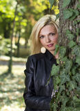 Beautiful blond woman hiding behind a tree. In nature Royalty Free Stock Images