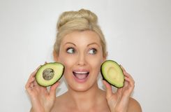 A beautiful blond woman is holding an avocado. Clean skin. Natural cosmetic. stock photography