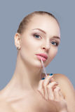 Beautiful blond woman holding pink lip gloss on gray background. lip makeup Stock Images