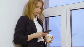 Beautiful blond woman holds coffee cup and uses mobile phone in business office stock video footage