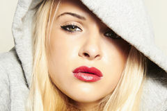 Beautiful blond woman in hood. red lips. Portrait of beautiful blond woman in hood. red lips Royalty Free Stock Photos
