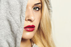 Beautiful blond woman in hood. red lips. Portrait of beautiful blond woman in hood. red lips Royalty Free Stock Images
