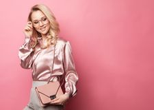 Beautiful Blond Woman In A Blouse And Pants Wearing Glasses, Holding Handbag Royalty Free Stock Photo
