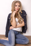 Beautiful blond woman in jeans and jacket Stock Images
