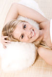 Beautiful blond woman laying and enjoying the spa. Smiling and relaxed beautiful blond woman laying on her back on a wicker mat and using a furry pillow, enjoys Royalty Free Stock Photo