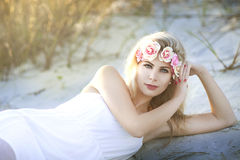 A beautiful blond woman laying in sand on Crescent Beach in Florida. Royalty Free Stock Photo