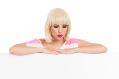 Beautiful blond woman lean at the banner and looking down. Stock Image