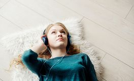 Beautiful blond woman listening to music through headphones Royalty Free Stock Photography