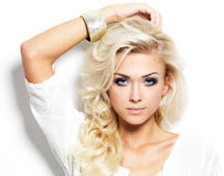 Beautiful blond woman with long curly hair and style makeup. Royalty Free Stock Photo