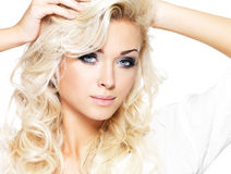 Beautiful blond woman with long curly hair and style makeup. Girl posing on white background stock images