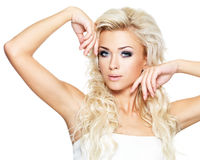 Beautiful blond woman with long curly hair and style makeup. Royalty Free Stock Image