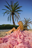 Beautiful blond woman with long legs in a pink ball gown Royalty Free Stock Images