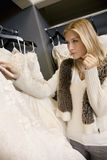Beautiful blond woman looking at price tag of wedding gown in bridal boutique Royalty Free Stock Photos