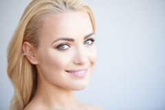 Beautiful blond woman with a lovely smile. Beautiful blond woman with a lovely gentle smile looking sideways at the camera on a grey background with copyspace Royalty Free Stock Image