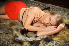 Beautiful blond woman lying on the chateau carpet Royalty Free Stock Photography