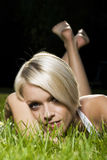 Beautiful blond woman lying on grass Stock Photo