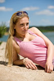 Beautiful blond woman lying on sunny beach Royalty Free Stock Image