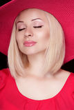 Beautiful blond woman with makeup, sensual girl posing in red ha Stock Photo