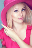 Beautiful blond woman with makeup, smiling girl posing in pink h Royalty Free Stock Photography
