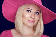Beautiful blond woman with makeup, smiling girl posing in pink h Stock Images