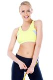 Beautiful blond woman measuring her waist Royalty Free Stock Photography