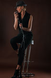 Beautiful blond woman with a microphone sitting on bar chair Stock Photography
