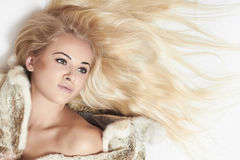 Beautiful blond woman in mink fur on the floor. long hair Royalty Free Stock Images