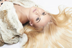 Beautiful blond woman in mink fur on the floor. long hair Stock Photo