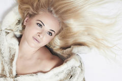 Beautiful blond woman in mink fur on the floor. long hair Royalty Free Stock Image