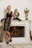 Beautiful blond woman near the fireplace Stock Image