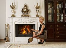 Beautiful blond woman near the fireplace Royalty Free Stock Photos