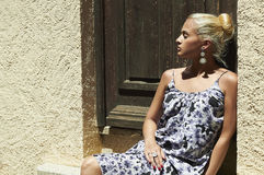 Beautiful blond woman near old wooden door.beauty girl in colored dress Stock Image