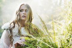 Beautiful blond woman next to the fern Royalty Free Stock Photography