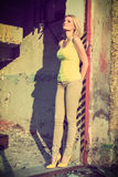 Beautiful blond woman next to a old building. Beautiful blonde in yellow shirt and jeans posing next to old building, fashion photography, cross processing Royalty Free Stock Photos
