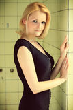 Beautiful blond woman in a old building. Beautiful blond woman in a dress posing in a old building, in a old shower stall, cross processing, fashion photography Royalty Free Stock Image