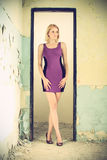 Beautiful blond woman in a old building. Beautiful blond woman in a purple dress posing in a old building, she stands between the doorjamb, cross processing Royalty Free Stock Image