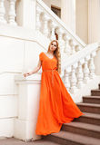 Beautiful blond woman in orange dress outdoors Stock Images