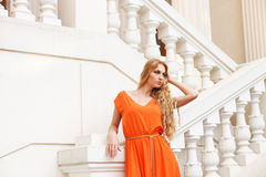 Beautiful blond woman in orange dress outdoors Royalty Free Stock Image