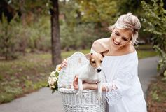 Beautiful, blond woman outdoors in a park with a pet dog Stock Photos