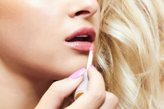 Beautiful blond woman paints lips with lipstick. lip gloss Royalty Free Stock Image