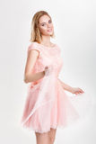 Beautiful blond woman in a pink cocktail dress dancing and havin Royalty Free Stock Photos